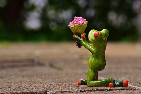 green frog holding bouquet of flowers figurine macro shot