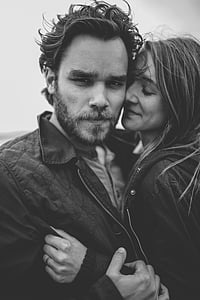 grayscale photography of woman embracing man