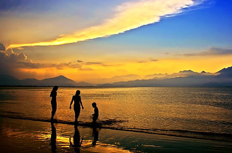 silhouette of three person walking on beach shore during sunset