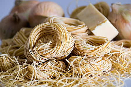uncooked pastas beside cheese and onions