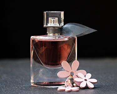 fragrance bottle beside three pink petaled flowers