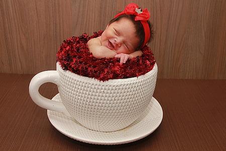 white ceramic mug and saucer with baby sleeping