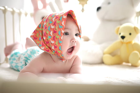 baby with pink head scarf prone lying in crib