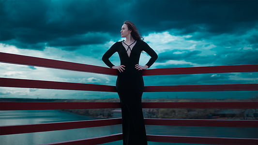 woman wearing black dress leaning on red railings