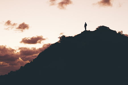 silhouette photo of man on top of hill