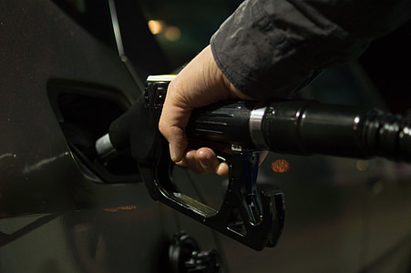 person holding black fuel nozzle mounted on car fuel tank