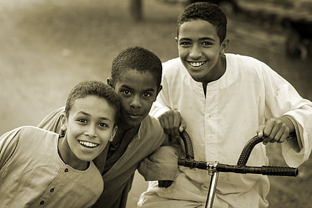three boy with bicycle