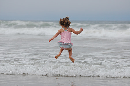 timelapse photography of girl jumping by the seashore