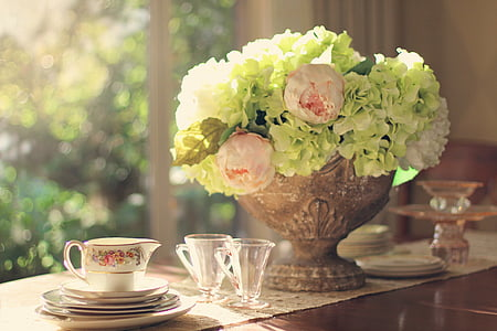 green hydrangea and pink buttercup flower arrangement and clear glasses