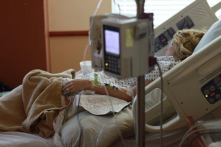 woman lying on hospital bed inside hospital
