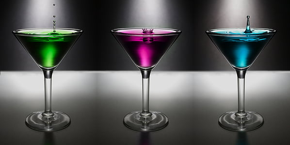 three cocktail glasses filled with assorted-color liquors