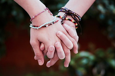 person's wearing multi-colored friendship bracelets