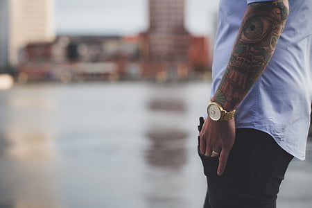 selective focus photography of man in white shirt, gold-colored analog watch, and black bottoms