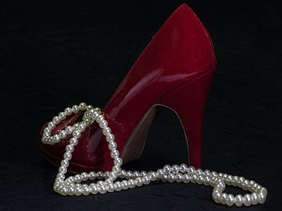 unpaired women's red leather stiletto with white pearl necklace
