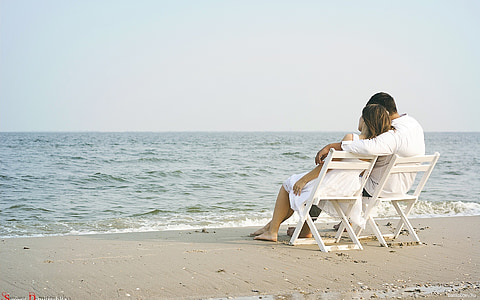 man and woman sitting on white wooden chairs beside the shore