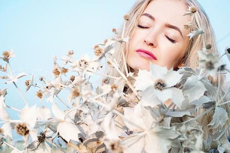 woman behind white petaled flower