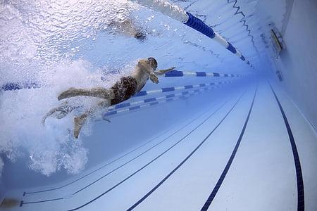 man swimming under pool