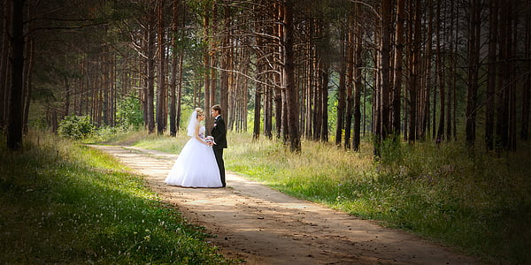 man and woman wearing wedding dress standing on road between trees
