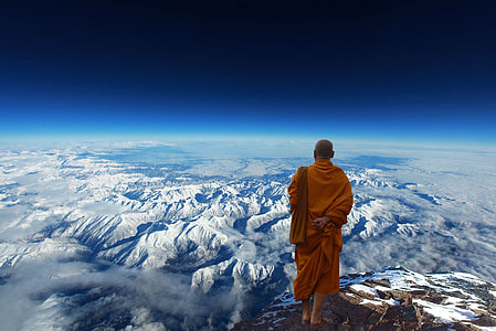monk standing on top of summit mountain
