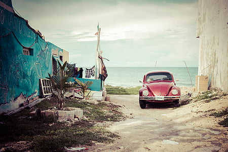 red Volkswagen Beetle in the beach during daytime
