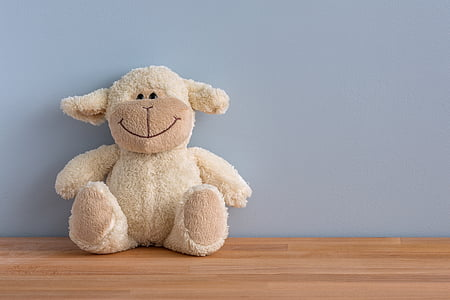 white sheep plush toy on brown wood flooring