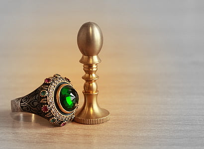 silver-colored ring with green gemstone