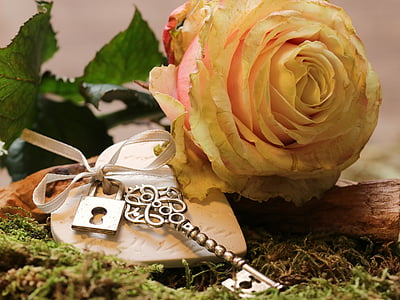 silver-colored key keychain with yellow flower