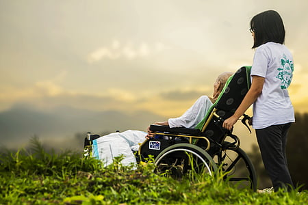 woman holding wheelchair with person during daytime