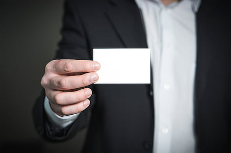 person holds white card