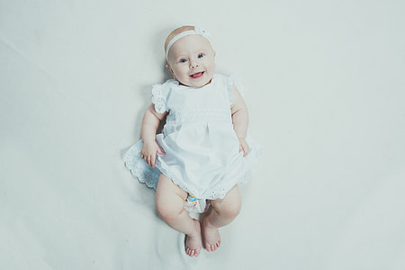 baby smiling wearing white headband and dress lying on bed