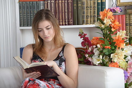 woman sitting on sofa while reading book