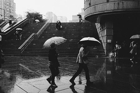 grey scale photography of people under umbrella