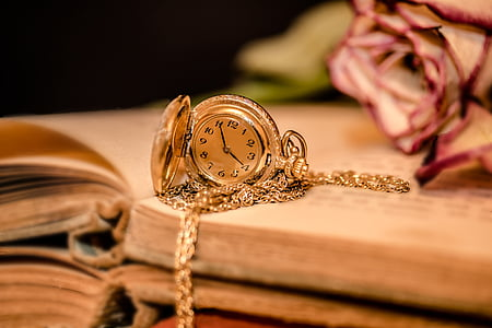 gold-colored analog pocket watch