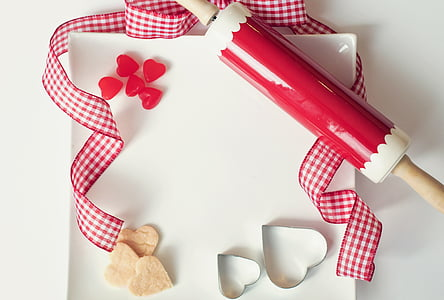 red and white rolling pin on white board