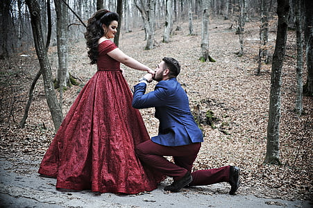man wears blue suit and women's red dress in the forest
