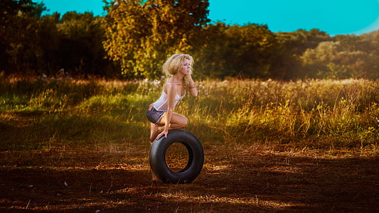 woman in white tank top holding vehicle tire
