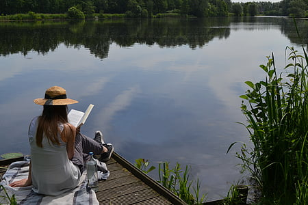 woman in gray sleeveless top reading book beside sitting on dock during daytime