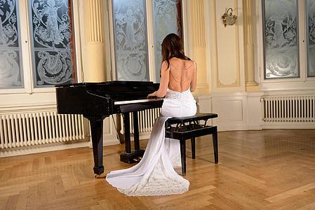 woman wearing white dress playing grand piano