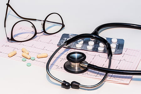 black stethoscope and eyeglasses on white surface