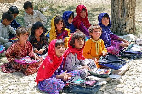children sitting on ground during daytime