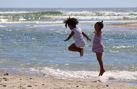 two child hopping near seashore
