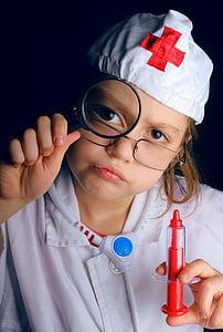 child wearing doctor costume holding syringe toy