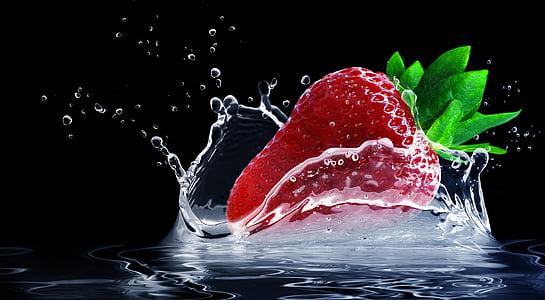 time lapse photography of strawberry splashing on water