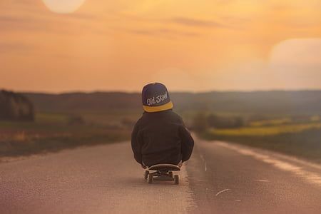 toddler on skateboard towards road during golden hour