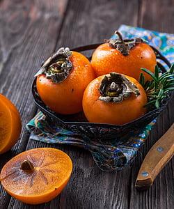 three round orange fruits on bowl