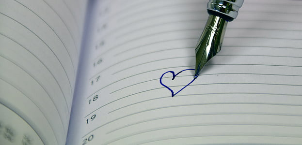 silver fountain pen drew a heart in white ruled paper