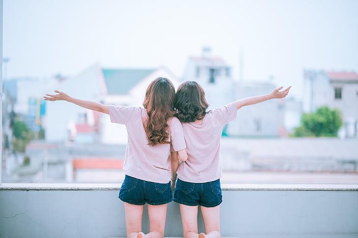 girl wearing white crew-neck shirt beside girl raising right arm