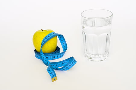 yellow fruit on tape measure near glass filled with water