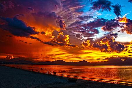people near ocean during golden hour