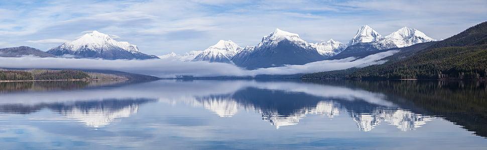 snow capped mountain mirror on lake during daytime